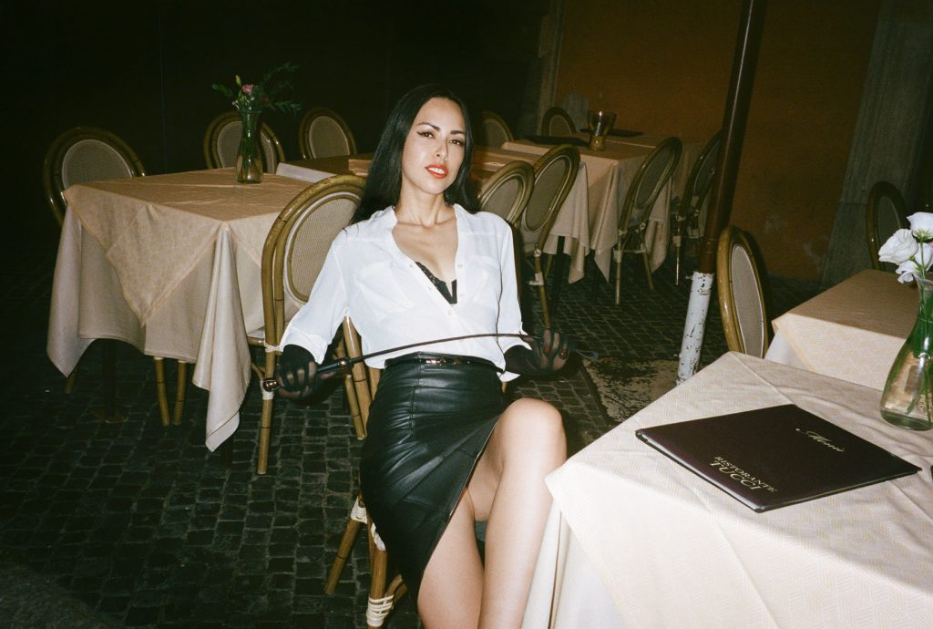 Femdomme Iris sits at a restaurant in Paris, France wearing mesh gloves and leather skirt holding a riding crop